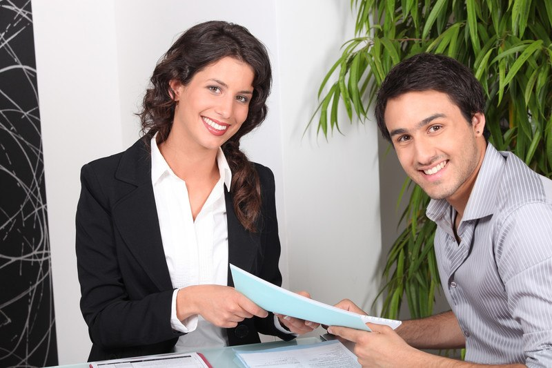 This photo shows a smiling dark haired woman in a black suit and white blouse handing some paperwork to a smiling dark haired man in a gray and white striped shirt.d