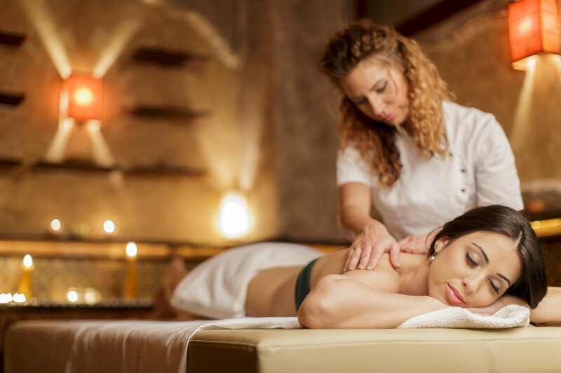 This photo shows a blonde massage therapist massaging the shoulders of a brunette woman who is lying face down on a massage table in a candle-lit room.