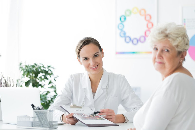 This photo shows a young woman in a white lab coat talking to an older woman and showing her information on a clipboard in a white office with a green plant and multicolored posters on the wall behind her.