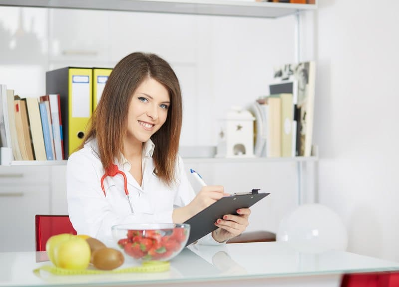 This photo shows a smiling brunette woman in a white lab coat with a pen and clipboard in a white office with books on shelves behind her and fresh fruit on a white table in front of her.