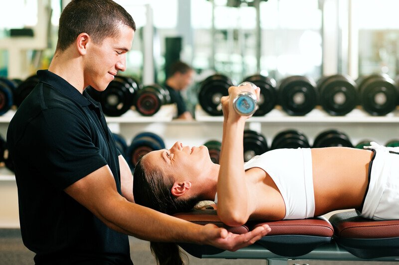 This photo shows a male personal trainer in black clothing helping a female client in white workout clothing as she lifts weights.