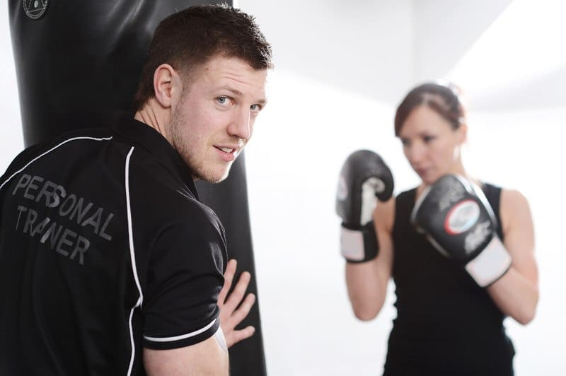 This photo shows a male personal trainer in black helping a female client in black work out with a punching bag and gloves.