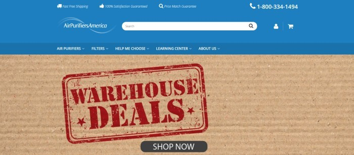 This screenshot of the home page for Air Purifiers America has a blue header and navigation bar with white text above a closeup photo of a piece of corrugated cardboard with a red stamped announcement for warehouse deals on it, along with a black call to action button.