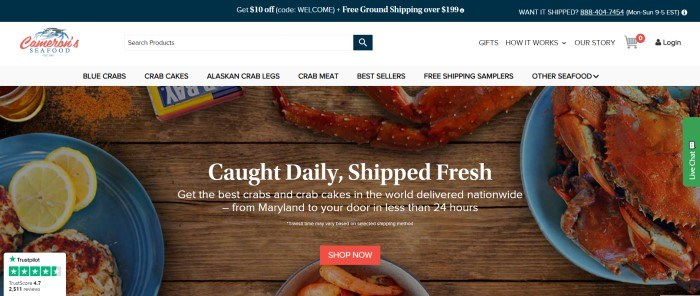 This screenshot of the home page for Cameron's Seafood has a dark blue header, a white search bar and navigation bar, and a large overhead photo showing crab legs on blue plates on a wooden table, along with white text and a red call to action button.