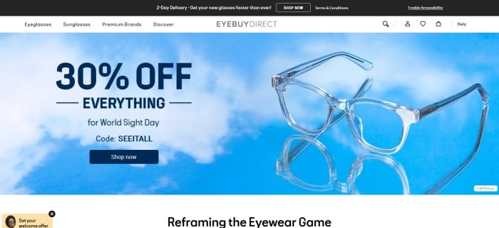 This screenshot of the home page for EyeBuyDirect has a black header, a gray navigation bar with black text, and a main section with a background of blue sky and white clouds behind a pair of blue plastic frames, blue text, and a dark blue call to action button.