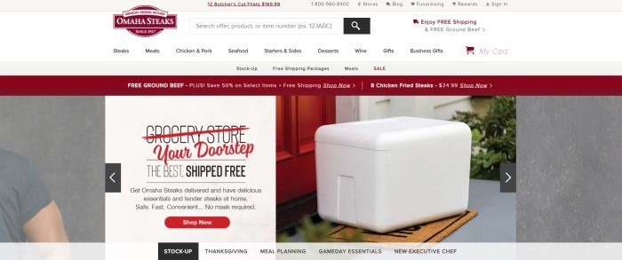 This screenshot of the home page for Omaha Steaks has a gray and white header with a burgundy logo and black text in the navigation bar, along with a burgundy announcement bar above two large photos showing the shoulder of a man in a gray tee shirt on the left side of the page and a white box of food on the stairs near a red door on the right side of the page, behind a white text box with black and red text and a red call to action button.