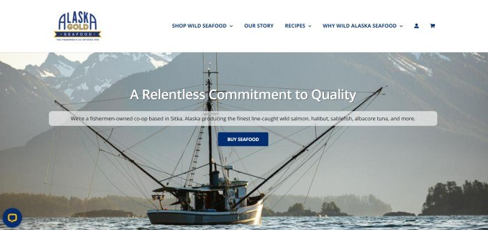 This screenshot of the home page for Alaska Gold Seafood has a white navigation bar with blue text and a blue and gold logo above a large filtered photo of a fishing boat on the water with mountains in the background, behind white and black text and a blue call to action button.