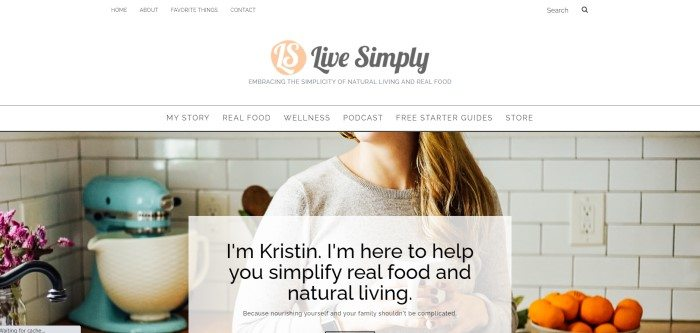 This screenshot of the home page for Live Simply has a white header and navigation bar with black text and a black and pink logo above a large photo showing the neck and torso of a woman with long blond hair and a tan sweater standing in a white-tiled kitchen with purple flowers, a bowl of oranges, and a blue stand mixer, behind a white text box with black text.