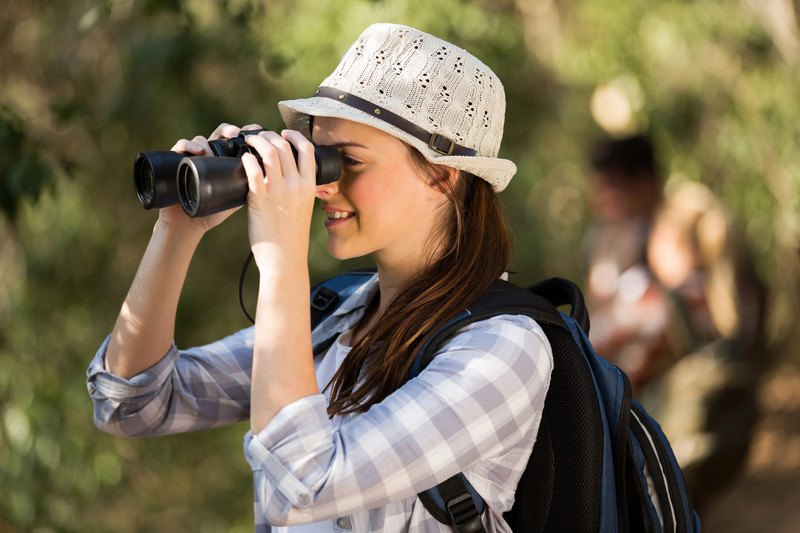 This photo shows a smiling brunette woman in a white hat and gray and white checked shirt looking through a pair of binoculars in a forest setting, representing the best bird watching affiliate programs.