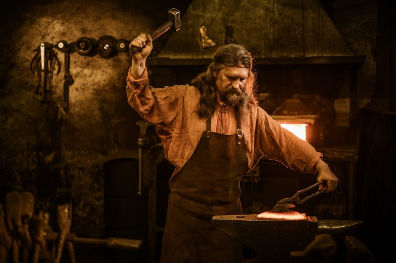 This photo shows a blacksmith in a forge swinging a hammer over his head as he aims toward a piece of glowing metal he is holding on an anvil with a pair of tongs, representing the best blacksmith affiliate programs.