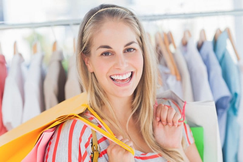 This photo shows a smiling blonde woman in a red and gray striped shirt holding yellow and green shopping bags in front of a row of shirts on a rack, representing the best budget fashion affiliate programs.