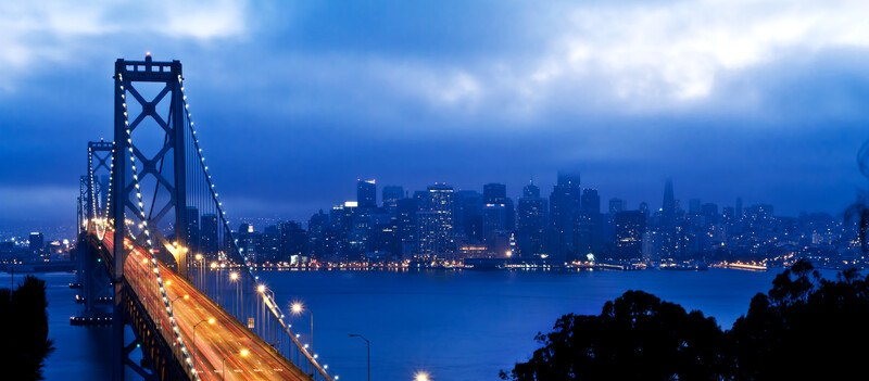 This photo shows the San Francisco skyline at night, complete with the lit Golden Gate Bridge, representing the best San Francisco affiliate programs.