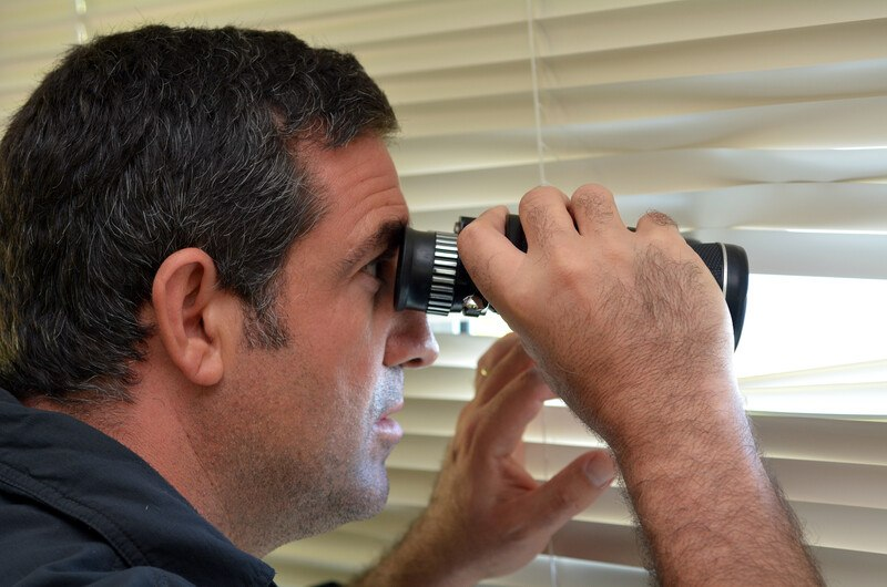 This photo shows a dark haired man in a dark shirt looking with binoculars through the blinds of a window, representing a bounty hunter at work surveilling a fugitive.