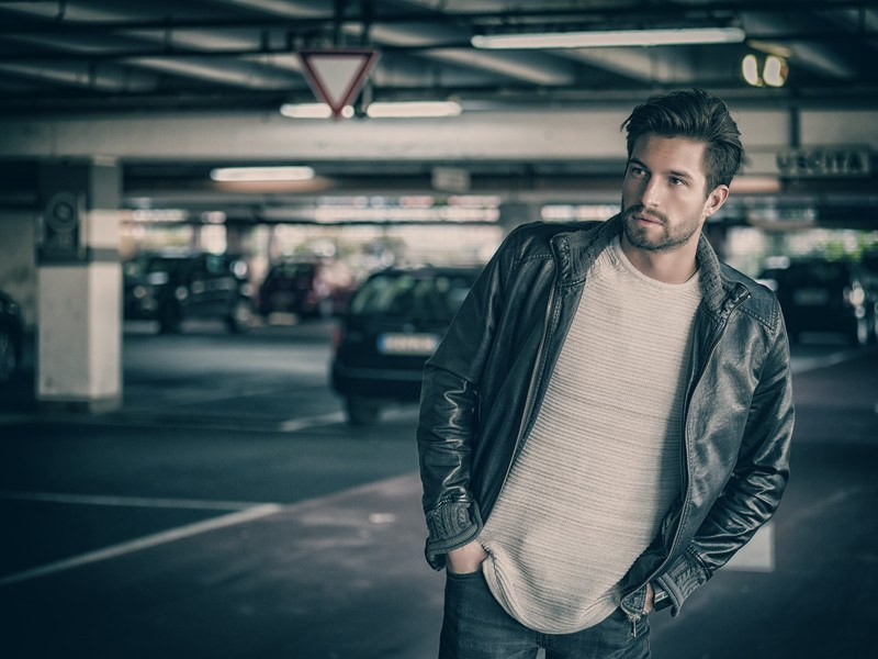 This photo shows a bearded young man in jeans, a white top, and a black jacket in an underground parking lot, representing a bounty hunter looking for a fugitive.