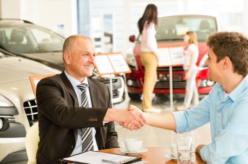 This photo shows a smiling man in a business suit shaking hands with a smiling man in a blue button down shirt as they sit at a table near some cars inside a dealership where a woman and a young girl are looking at a red car.