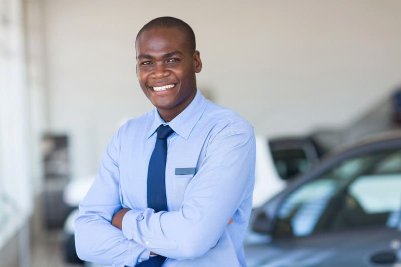 This photo shows a smiling man in a blue shirt and tie standing next to a gray car inside a car dealership.
