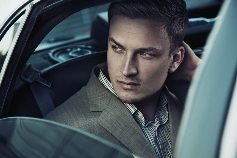This photo shows a young man in a striped shirt and business jacket looking out of a car window, representing the question, do bounty hunters make good money?
