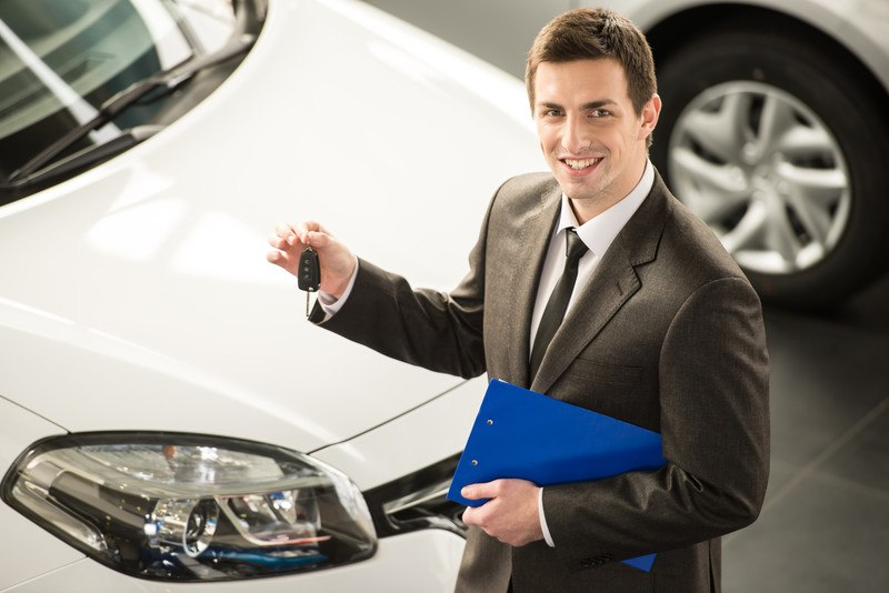 This photo shows a smiling young car salesman in a dark suit holding a set of keys as he stands next to a white car.