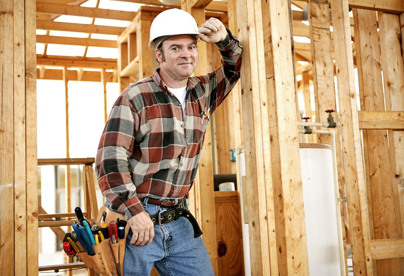 This photo shows a smiling man in a white hard hat and an orange and black plaid shirt with a tool belt leaning up against a framed wall in a new building, representing the question, do carpenters make good money?