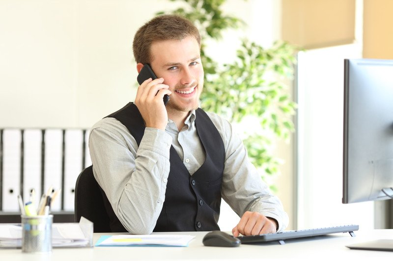 This photo shows a smiling young man dressed in a button down shirt and dress talking on the telephone with an open file in a brightly lit office, representing the question, do insurance adjusters make good money?