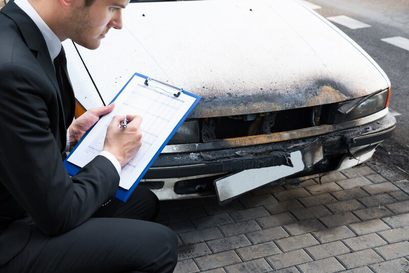 This photo shows a young man in a dark business suit looking at damage tot eh bumper of a white car as he writes on a paper held on a clipboard, representing an insurance adjuster at work.