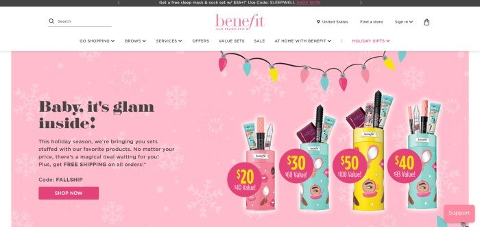 This screenshot of the home page for Benefit Cosmetics has a black announcement bar, a white navigation bar with pink and black text, and a pink main section with black text and a pink call to action button on the left side of the page, with a row of photo inserts of value sets and graphics of holiday lights on the right side of the page.
