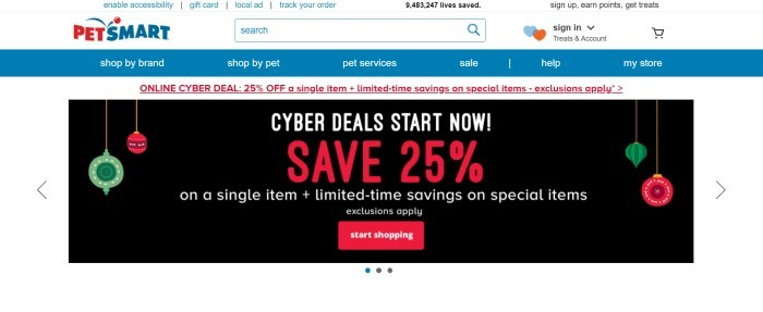 This screenshot of the home page for PetSmart has a white header with blue text, a blue navigation bar with white text, an announcement section with red text, and a main announcement section with a black background, green and red ornament graphics, and red and white text, as well as a red call to action button.