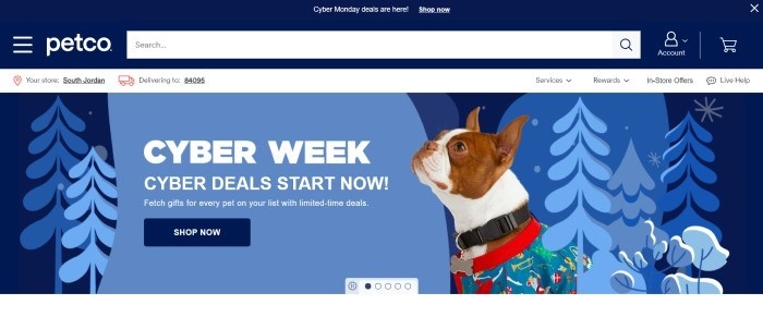 This screenshot of the home page for Petco has a navy blue header and search bar above a blue graphic background showing a forest landscape behind an overlaying photo of a dog in a multicolored sweater, along with white text and a navy blue call to action button.