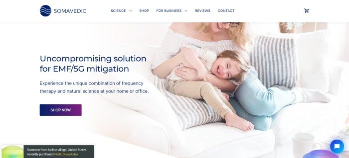 This screenshot of the home page for Somavedic Technologies has a white navigation bar with a blue logo and blue text above a photo on the right side of the page showing a smiling blonde woman in glasses and a white shirt playing with a child on white couch with striped gray and white pillows, and a white section with blue text and a photo insert of a Somavedic device on the left side of the page, as well as a blue call to action button.