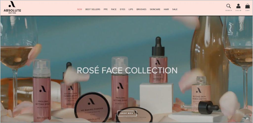 This screenshot of Absolute New York homepage shows a pink colored header with logo at the left side, navigational menu at the center, and search, account, and shopping bag icon at the right side, header image of a collection of makeup with a bottle of wine and a couple of wine glass.