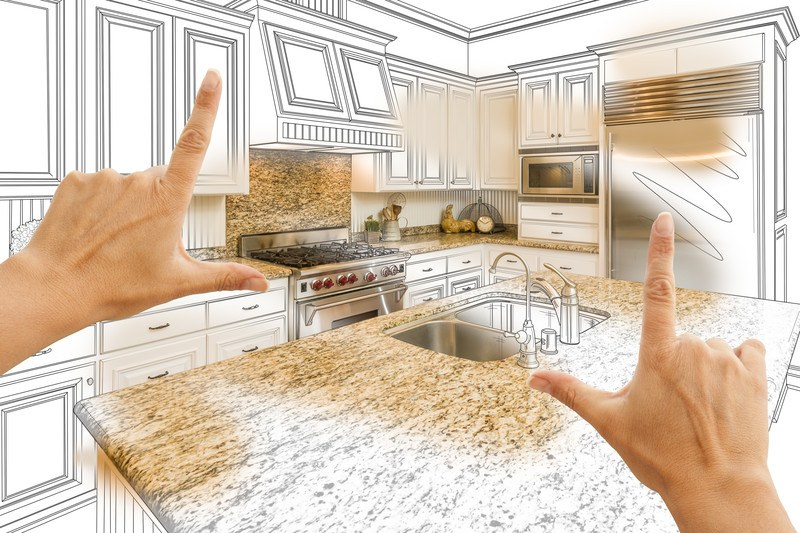 This photo shows a picture of two hands creating a frame to show a black and white line drawing of a kitchen with the countertops, refrigerator, backsplash, and microwave filled in, representing the best kitchen & bath remodel affiliate programs.