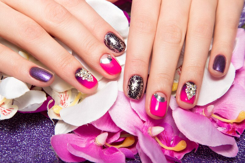 This photo shows a pair of female hands with purple, pink, and gold nail art on the fingernails, resting on a bed of pink silk flowers, representing the best nail art affiliate programs.