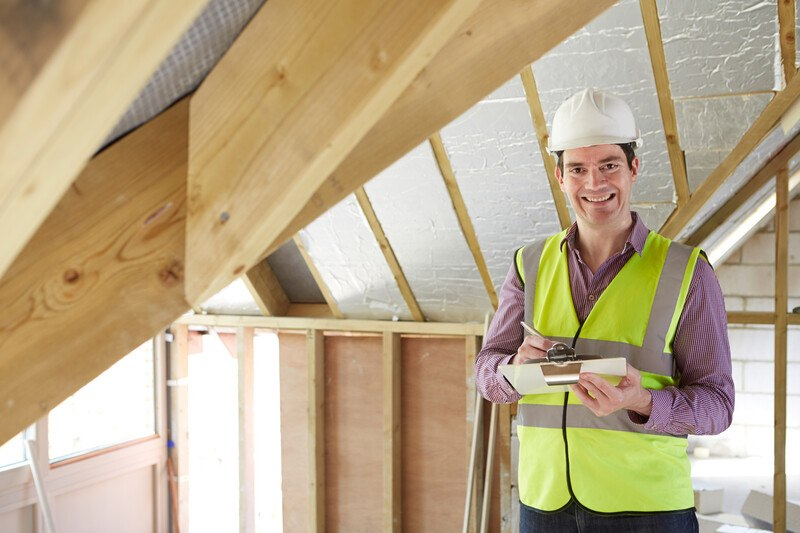 This photo shows a smiling man in a white hard hat, purple shirt, and yellow construction shirt writing on a clipboard near the attic ceiling of an unfinished home, representing the question, do home inspectors make good money?