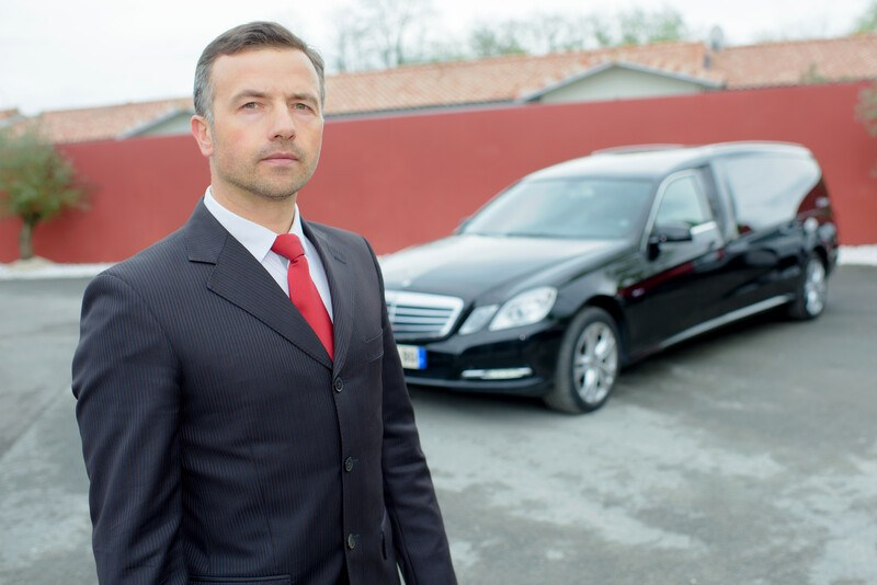 This photo shows a serious-faced man in a dark suit and red tie standing in front of a dark hearse in a parking lot, representing the question, do morticians make good money?