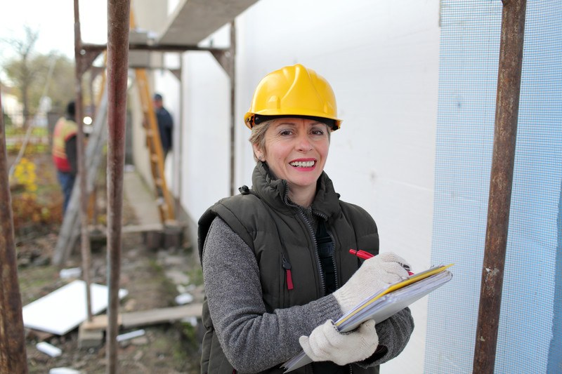 This photo shows a smiling woman in a yellow hard hat, a gray sweater and black coat vest, and white gloves, writing something on a yellow clipboard while construction workers work in the background.