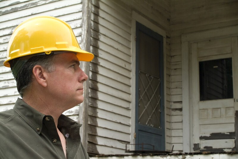 This photo shows a serious faced man in a yellow hard hat looking at the outside of a run-down white house.