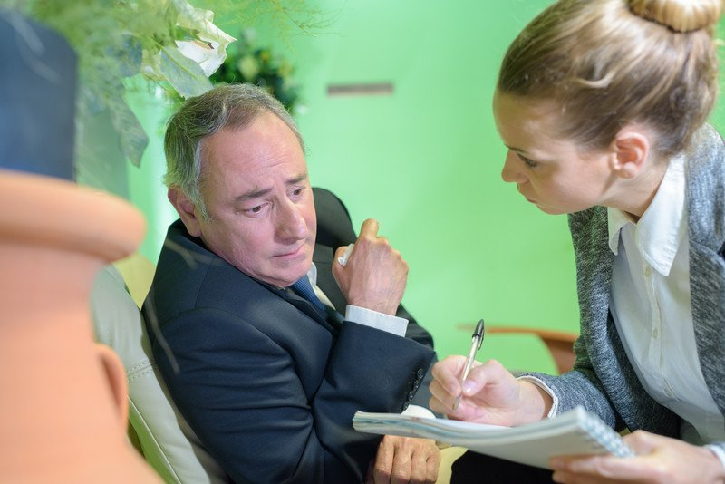 This photo shows a sad-faced elderly gentleman in a dark suit talking with a blonde female mortician with a white shirt and gray jacket as she takes notes, in a green room, representing a mortician at work.