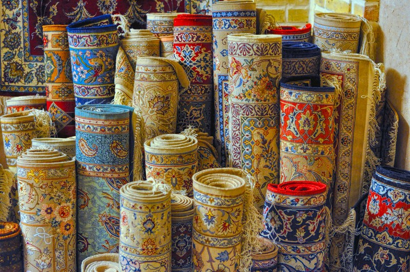 This photo shows several rolled up detailed carpets in gold, red, and blue colors, representing the best rug and carpet affiliate programs.