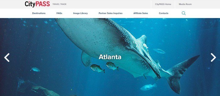 This screenshot of the home page for CityPASS has a gray header, a white navigation bar with black text, and a photo of fish and a shark in an aquarium in Atlanta behind white text.