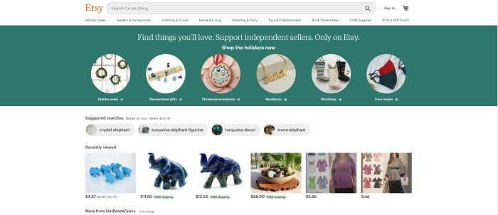 This screenshot of the home page for Etsy has a white navigation bar and search bar above a green announcement section with a row of categories with circular images showing types of products to shop for, above a white main section with photos showing product images for suggested searches and recently searched items.