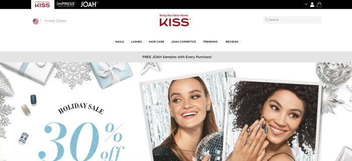 This screenshot of the home page for Kiss has a black header, a white navigation bar, a gray announcement bar, and a main section with a white background, silver snowflakes, white and blue wrapped gifts, two photo inserts showing smiling women with beautiful decorated nails, and black and blue text.