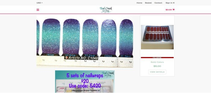 This screenshot of the home page for Teal Creek Nail Wraps has a gray header and navigation bar with red elements above a closeup photo showing blue sparkly nail wraps in the center and left side of the page, a package of orange solid wraps on the right side of the page, and a sales announcement box in teal with a photo of several products and blue text at the bottom of the page.