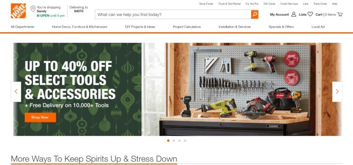 This screenshot of the home page for The Home Depot has a white header and navigation bar above a split main section with a photo of a tool bench and several tools hanging on the wall on the right side of the page and a green graphic section with white lettering on the left side of the page, along with an orange call to action button.