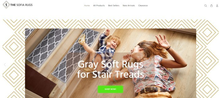 This screenshot of the home page for The Sofia Rugs has a white navigation bar with black text above a main section that includes a background with gold-outlined nested white squares and a photo of a smiling mom and toddler lying on a wooden floor next to wooden stairs with gray and white stair treads on them, as well as white text and a green call to action button.