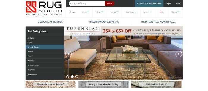 This screenshot of the home page of Rug Studio has a dark search bar above a white navigation bar, with a black category column on the left side of the main section of the page and a photo of a living room with a glass coffee table on a large beige, cream, and red area rug.