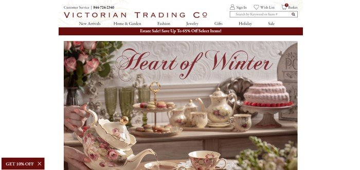 This screenshot of the home page for Victorian Trading Company has a white background with black and maroon text in the search bar and navigation bar, above a maroon sales bar and a main section with a photo of a Victorian table setting with cake, a floral porcelain tea set, and a vase of roses on the table, along with a maroon call to action button.