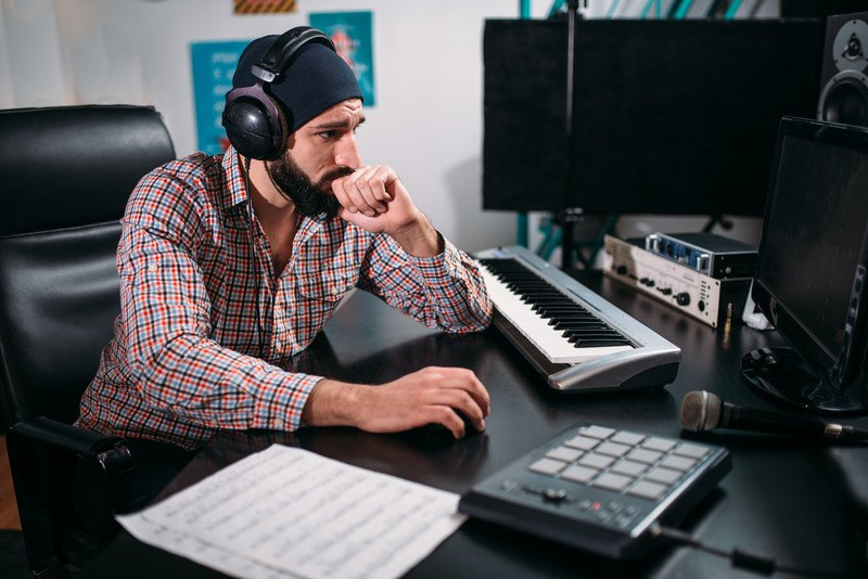 This photo shows a bearded man in a black beanie, headset, and multicolored button down shirt working on a computer near a piano keyboard, high tech equipment, and sheets of music.