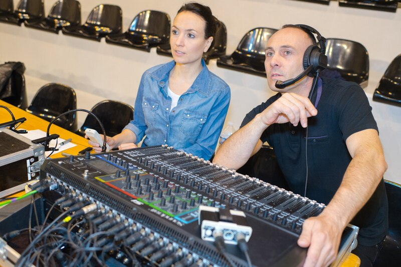 This photo shows a woman in a blue shirt and a man in a black shirt sitting in a recording studio behind high tech audio equipment.