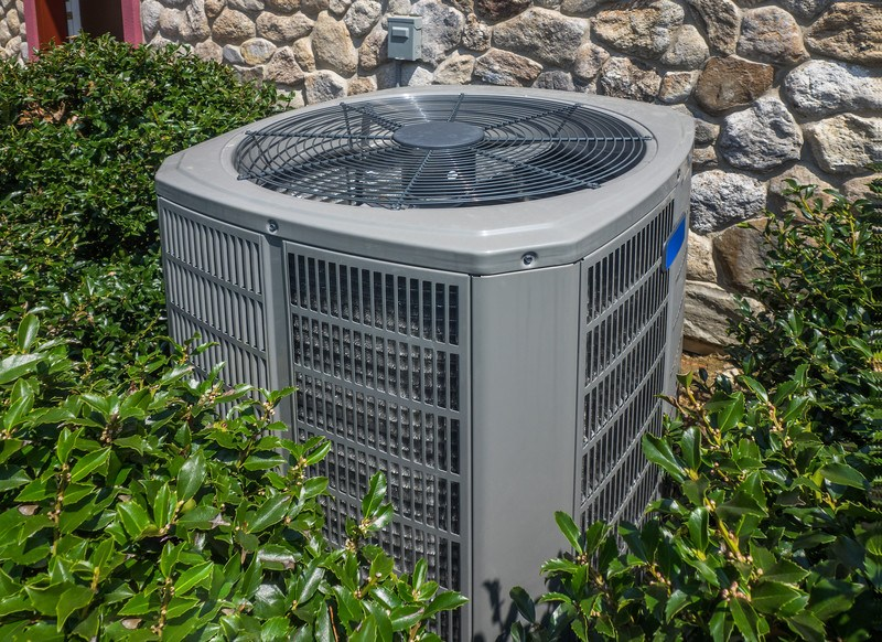 This photo shows a central air unit outside a rock-walled home, surrounded by Holly, representing the best HVAC affiliate programs.