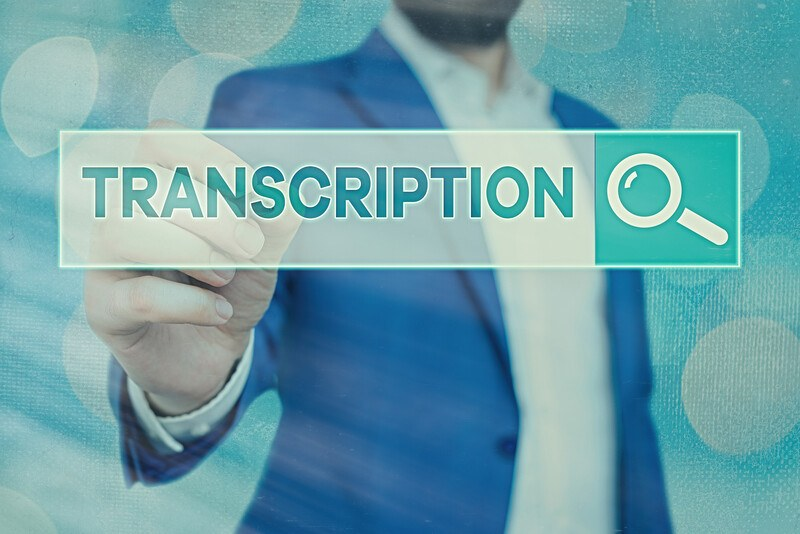 This image shows a neck-to-waist photo of a man in a blue business suit in front of a blue background, stretching forth his hand to touch a white and teal call to action button with the word 'transcription' on it, floating in front of him across the middle of the page, representing the best transcribing affiliate programs.